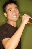 Young man raising beer bottle - Alex Microstock02