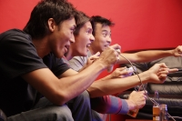 Young men holding video game controllers, making hand signs - Alex Microstock02
