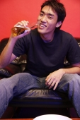 Young man drinking from beer bottle, looking at camera - Alex Microstock02