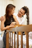 Couple standing over crib, looking at each other - Alex Microstock02