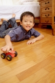 Young boy lying on floor with toy, looking at camera - Alex Microstock02