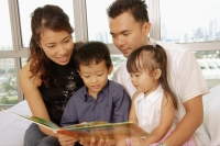 Family with two children sitting together, looking at book - Alex Microstock02