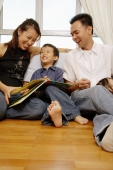 Family with one son sitting together, looking at book - Alex Microstock02
