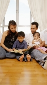 Parents with son and daughter sitting together, reading a book - Alex Microstock02