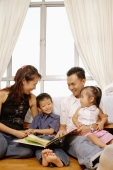 Parents with son and daughter sitting together, bonding - Alex Microstock02