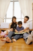 Parents reading with son, daughter looking at camera - Alex Microstock02