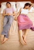 Couple lying in bed, side by side - Alex Microstock02