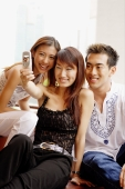 Two young women and one young man looking at camera phone - Alex Microstock02