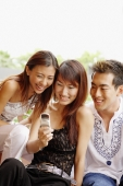 Young women and young man looking at mobile phone, smiling - Alex Microstock02