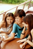Young women smiling, looking at mobile phone - Alex Microstock02