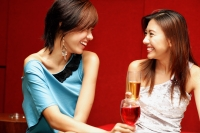 Two young women, with drinks, facing each other - Alex Microstock02