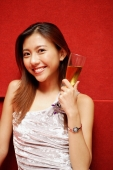 Young woman holding champagne glass, smiling at camera - Alex Microstock02