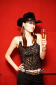 Young woman wearing cowboy hat, holding champagne glass, looking at camera - Alex Microstock02