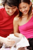 Couple sitting side by side, looking at magazine - Alex Microstock02
