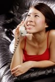 Young woman lying on sofa, using telephone - Alex Microstock02