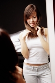 Young woman looking at mirror, touching her hair - Alex Microstock02