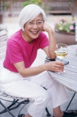 Mature woman sitting outdoors with wine glass, looking at camera - Mary Grace Long