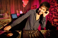 Young man spinning at club, smiling - Alex Microstock02