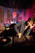 Young man spinning at club, using headphones - Alex Microstock02