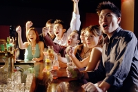 Group of friends sitting at bar, watching something - Alex Microstock02