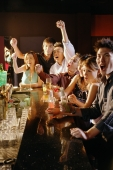Group of friends sitting at bar, arms raised - Alex Microstock02