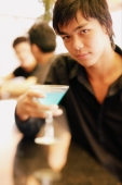 Young man at bar counter holding cocktail glass - Alex Microstock02