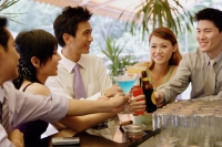 Young adults at bar counter toasting with drinks - Alex Microstock02