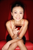 Woman sitting on chair, holding cocktail glass, looking at camera - Alex Microstock02