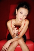 Woman sitting on chair, holding cocktail glass - Alex Microstock02
