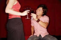 Couple toasting with drinks, man sitting looking up at woman standing in front of him - Alex Microstock02
