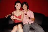 Couple sitting side by side, holding drinks, looking at camera - Alex Microstock02