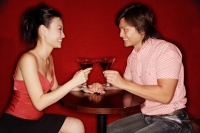 Couple sitting face to face, toasting with drinks - Alex Microstock02