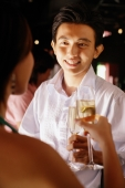 Couple at night club, holding champagne glasses, man facing woman - Alex Microstock02