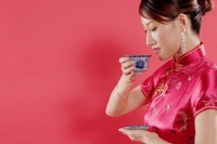 Woman holding teacup, looking down, sideview - Alex Microstock02