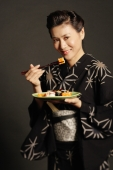 Woman in Japanese costume, holding chopsticks and eating sushi - Alex Microstock02