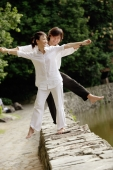Couple balancing along ledge, arms outstretched - Alex Microstock02