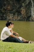 Couple sitting on grass, looking away - Alex Microstock02