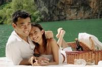 Couple having picnic by a lake, looking at camera - Alex Microstock02