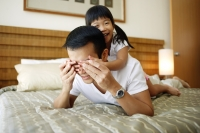 Little girl covering father's eyes with hands - Jade Lee