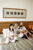 Three generation family on bed, looking at camera - Jade Lee