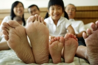 Three generation family on bed, focus on their feet - Jade Lee