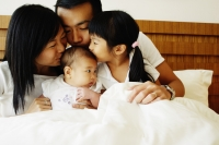 Father, mother and daughter kissing baby - Jade Lee