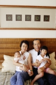 Grandparents with grandchildren, sitting on bed, looking at camera - Jade Lee