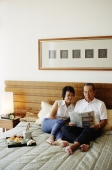 Older couple lying on bed, reading newspaper - Jade Lee