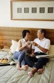 Older couple lying on bed, toasting with tea - Jade Lee