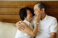 Older couple, hugging, woman with hand on man's face - Jade Lee