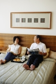 Older couple lying on bed, tray of food between them - Jade Lee