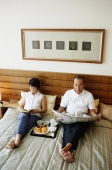 Older couple lying on bed, reading newspaper, tray of food between them - Jade Lee
