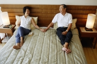 Older couple lying on bed, holding hands - Jade Lee