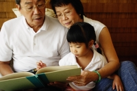 Grandparents with granddaughter, reading a book - Jade Lee
